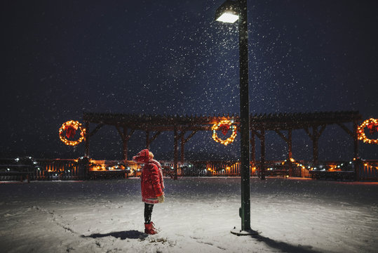 Girl standing looking at street light on snowy landscape