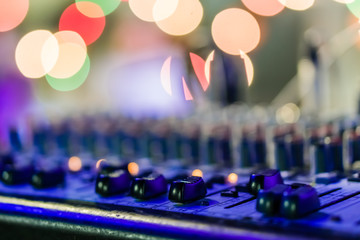 Selective focus on knops of electronic sound mixer in the foreground of the outdoor party music with bokeh.