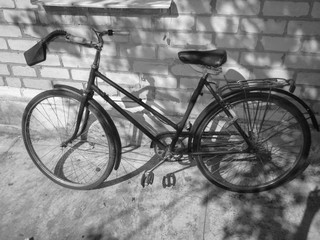 Old retro bicycle on brick wall. Photo in black and white style