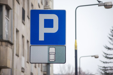 Parking sign. Vehicles take up way too much space in cities. Metropolis parking problems. Cars became biggest problem for urban ecology due emission and environmental pollution.