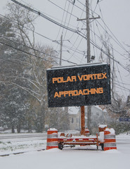 Road sign in snow warning of polar vortex