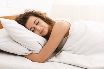 Young woman sleeping in bed in morning
