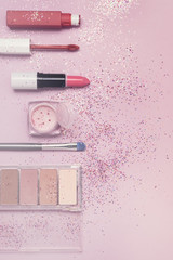 Sale Concept with Decorative Cosmetics on Pink Background Flat lay Top View Lipstick Eye Shadows Copy Space Toned