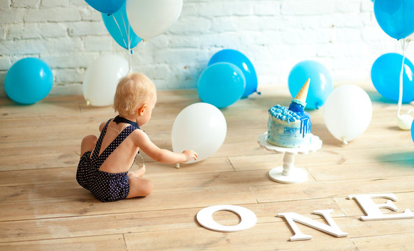 One year old boy is celebrating his first birthday among a balloons and festive cake.