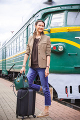 smiling middle-aged woman with luggage near old train