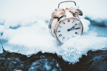 Frozen time. A clock on an ice next to the water. Extreme weather situation. Snow falling on a clock in a nature. Golden old clock.