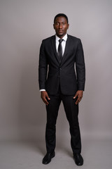 Young handsome African businessman against gray background