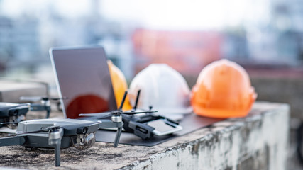 Drone, remote control, laptop computer, smartphone and protective helmet at construction site. Using unmanned aerial vehicle (UAV) for land and building site survey in civil engineering project.