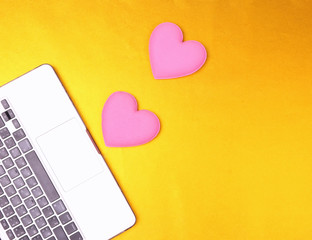 Computer keyboard and pink hearts on yellow glod background. Valentine day concep