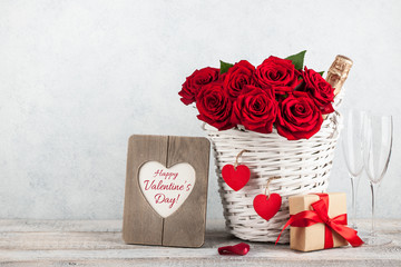 Valentine's day card with red roses, gift box and champagne bottle