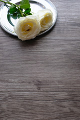 White roses on vintage round silver plate on wooden plank floor with copy space for valentine's day wedding ceremony