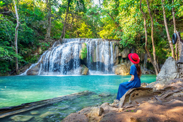 Wall Mural - Woman sitting at Erawan waterfall in Thailand. Beautiful waterfall with emerald pool in nature.