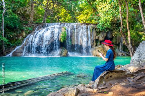 Wall mural Woman sitting at Erawan waterfall in Thailand. Beautiful waterfall with emerald pool in nature.