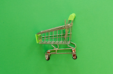 empty shopping cart on green background