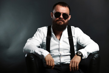 young handsome man with big beard and black sunglasses on black background