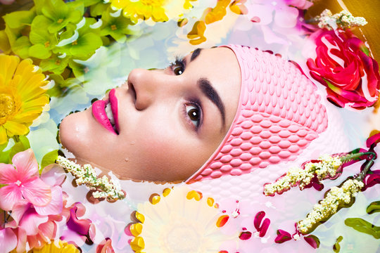 Portrait of a young woman floating in a pool of water surrounded by flowers.