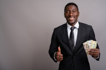 Young handsome African businessman holding money and smiling