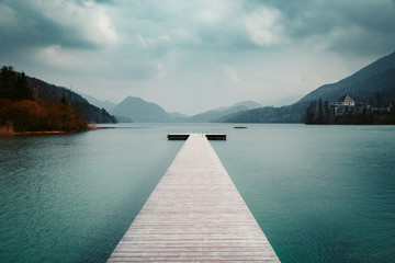 Wooden pier with clear lake in the Alps in summer Wall mural