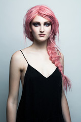 Portrait of a young woman wearing a pink wig and strong make up.