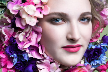Beautiful, young woman's face with red lipstick surrounded by colorful flowers, close up.