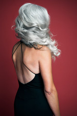 Beautiful woman wearing a black evening dress with long, silvery, grey hair, back view.