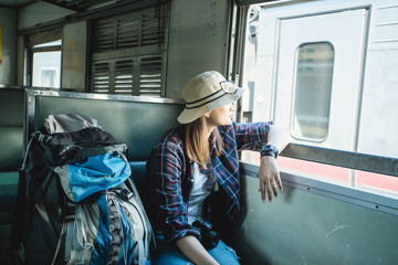 Young asian woman are waiting time to go travel by train in Thailand in planning holiday, Woman and backpacker travel alone in her weekend