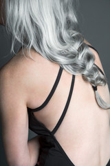 Back view of a beautiful woman wearing a black swimsuit with long, silvery, grey hair, cropped.