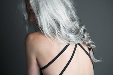 Back view of a beautiful woman with long, silvery, grey hair in her late fifties wearing a black swimsuit.