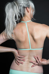 Back view of a beautiful woman with long, silvery, grey hair wearing a teal colored bikini, cropped.