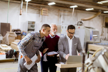 Three men standing and discuss in furniture factory