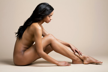 Beautiful, young, black woman sitting naked on a beige background touching her leg, full length.