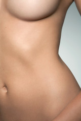 Closeup view of a naked woman's torso.