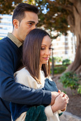 A man hugs his wife from behind in a public park