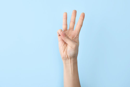 Woman showing W letter on color background, closeup. Sign language