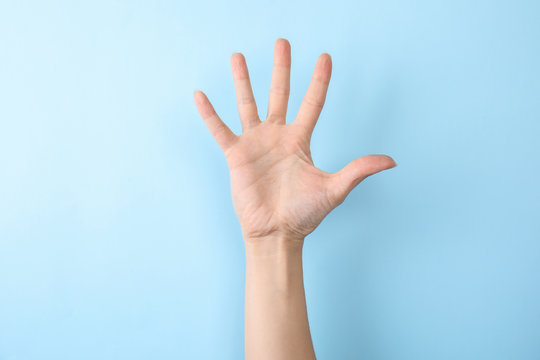 Woman showing number five on color background, closeup. Sign language
