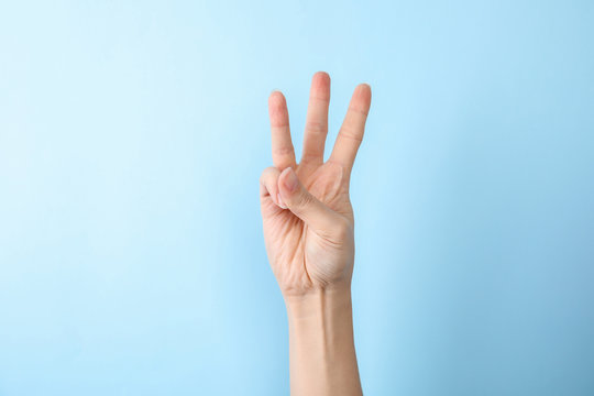 Woman showing number six on color background, closeup. Sign language