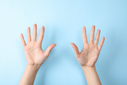Woman showing sign ten on color background, closeup. Body language