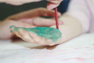 a three-year-old girl in a creative game with watercolor.-image