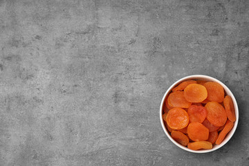 Bowl of dried apricots on grey background, top view with space for text. Healthy fruit