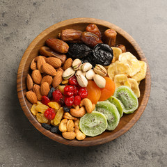 Plate with different dried fruits and nuts on table, top view