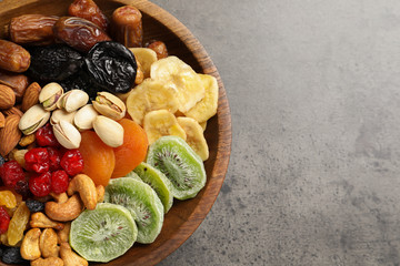 Plate with different dried fruits and nuts on table, closeup. Space for text