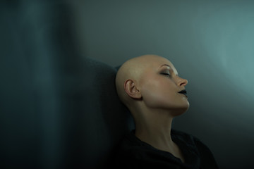 Emotive photo of a beautiful bald woman while sitting on a chair in a black tshirt.