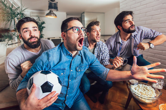 Men watching sport on tv together at home screaming cheerful.