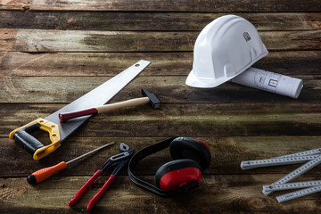 safety ear protection and many tools over wood background
