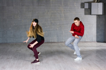 Attractive couple dancing social dance. Couple of young man and woman dancing hip-hop on grey studio background.