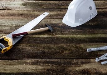 Construction helmet with saw, hammer and ruler for builder concept