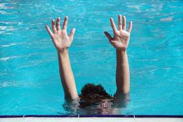 The boy in the pool under the water raised his hands up above the water.