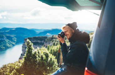 Wall Mural - hipster tourist hold in hands taking photography click on retro vintage photo camera in auto, photographer looking on camera technology, panoramic landscape vacation concept, sun flare mountain