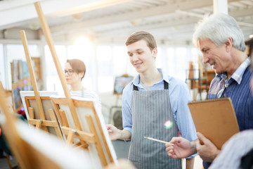 Waist up portrait of smiling teenage boy painting picture on easel in art studio, copy space