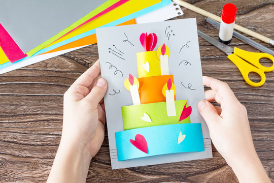 The child holds Greeting card with birthday cake congratulation. Children's art project craft for kids. Craft for children.